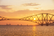 United Kingdom, Scotland, Firth of Forth, Forth Rail Bridge with tug boats underneath and Hound Point Oil Loading Marine Terminal at sunset - SMAF01046
