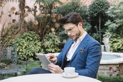 Elegant businessman using tablet in a garden cafe - ALBF00539