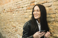 Smiling young woman with cell phone at brick wall looking around - ALBF00569