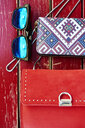 Sunglasses, purse and handbag on red wooden bench - ABIF00644