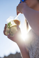 Woman drinking lemonade from plastic cup, close-up - ABIF00650