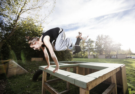 Woman jumping over barrier during freerunning exercise - CVF00855