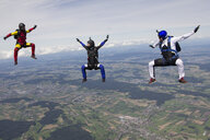 Team of three skydivers in sit fly position over Buttwil, Luzern, Switzerland - CUF33643