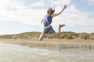 Girl jumping mid air on beach, Camber Sands, Kent, UK - CUF33715