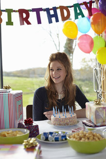 Teenage girl at  table with birthday cake - CUF33784