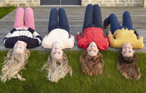 Four teenage girls lying on patio and looking back - CUF33790