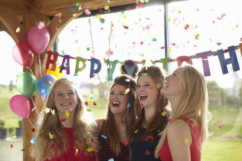 Four teenage girls enjoying confetti at birthday party - CUF33811