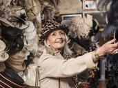 Glamorous senior woman looking at hats - CUF33817
