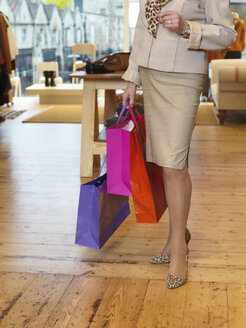 Glamorous senior woman with shopping bags in boutique - CUF33823