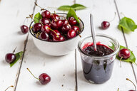 Jar of cherry jam and cherries on white wood - SARF03802