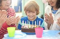Mother and children enjoying birthday celebration - CUF33932