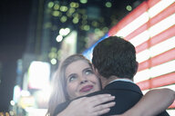 Neon american flag and young couple hugging, New York City, USA - CUF33956