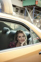Young woman sightseeing from yellow cab, New York City, USA - CUF33959