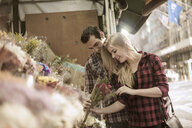 Young couple choosing flowers at flower stall - CUF33965