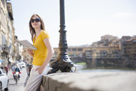Woman on riverside in Florence, Italy looking at map - CUF33980