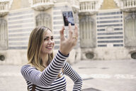 Young woman taking self portrait outside Museum of Ceramics, Valencia, Spain - CUF33995