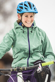 Portrait of smiling mid adult female mountain biker on bike - CUF34016