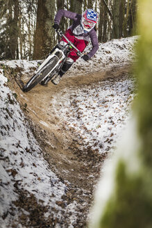 Young female mountain biker riding a forest dirt track - CUF34022