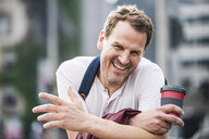 Portrait of happy man with takeaway coffee in the city - UUF14270