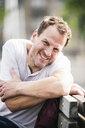 Portrait of smiling man sitting on bench - UUF14276