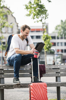 Smiling man with rolling suitcase and takeaway coffee sitting on bench using tablet - UUF14279