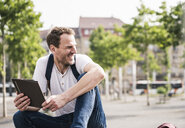 Smiling man sitting outdoors with tablet - UUF14282
