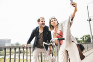 Happy couple taking a selfie on a bridge - UUF14303