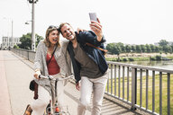 Happy couple taking a selfie on a bridge - UUF14306