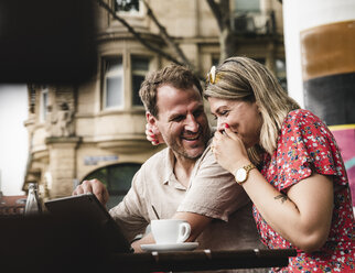 Happy couple with tablet at an outdoor cafe - UUF14309