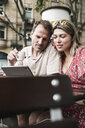 Couple looking at tablet at an outdoor cafe - UUF14312
