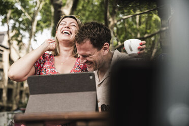 Happy couple with tablet at an outdoor cafe - UUF14315