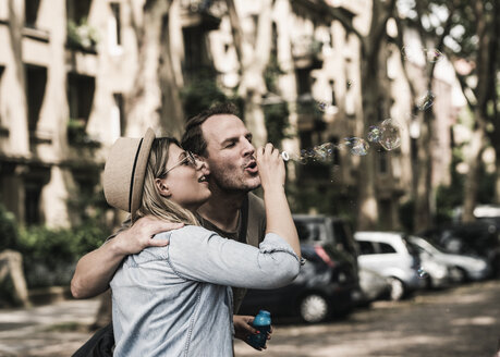 Couple blowing soap bubbles in the city together - UUF14321