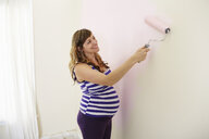 Pregnant woman painting nursery walls pink - ISF14239