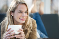 Mid adult woman relaxing on sofa with coffee - CUF34344