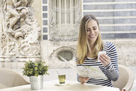 Young woman looking at smartphone outside Museum of Ceramics, Valencia, Spain - CUF34368