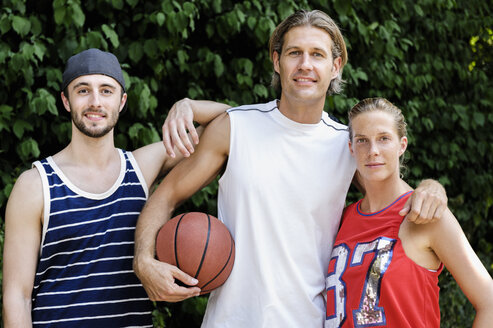 Portrait of three basketball players in park - CUF34434