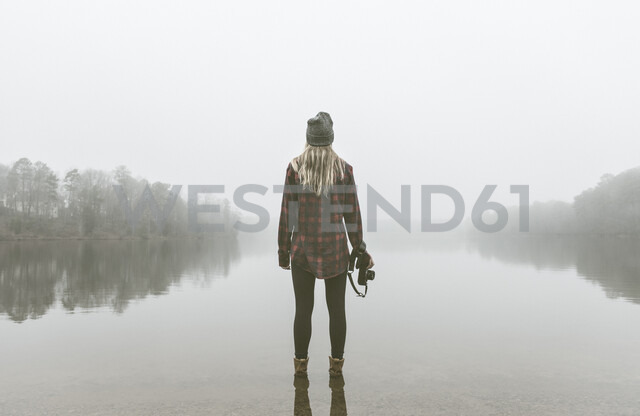 Young woman with camera standing in misty lake - ISF14260 - Corey Jenkins/Westend61