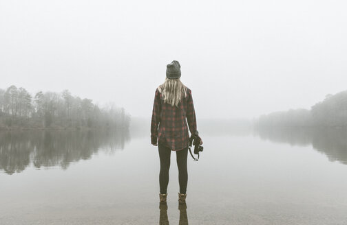 Young woman with camera standing in misty lake - ISF14260