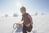 Young boy running, pulling sled - ISF14323
