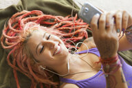 Close up of young woman with pink dreadlocks choosing music on smartphone - ISF14326