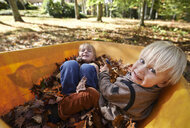 Two boys sitting in wheelbarrow full of leaves - ISF14335