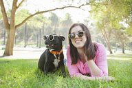 Portrait of young woman and dog lying in park wearing sunglasses - ISF14356