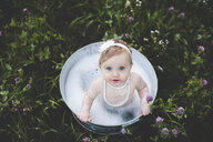 Overhead view of baby girl bathing in a tin bathtub in a wild flower meadow - ISF14368