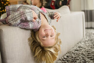 Portrait of boy lying upside down over sofa at christmas - ISF14371