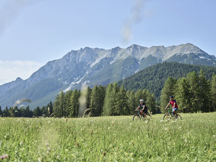 Austria, Tyrol, Mieming, couple riding bike in alpine scenery - CVF00860