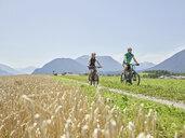 Austria, Tyrol, Mieming, couple riding bike in alpine scenery - CVF00863