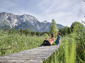 Austria, Tyrol, Mieming, couple resting on a boardwalk in the mountains - CVF00869