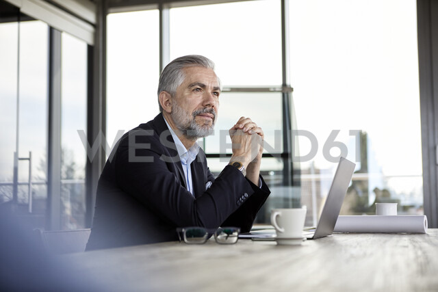 Businessman with laptop at desk in office thinking - RBF06303