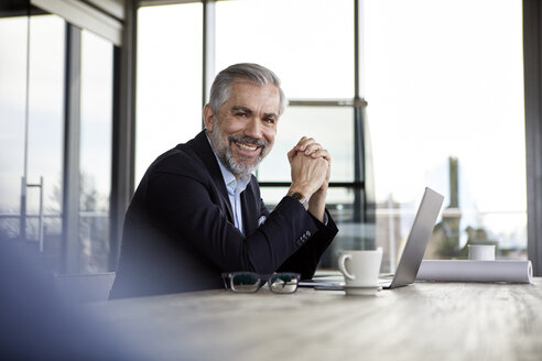 Portrait of smiling businessman with laptop at desk in office - RBF06306