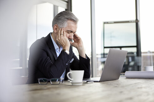 Businessman with headaches sitting at desk in office - RBF06309